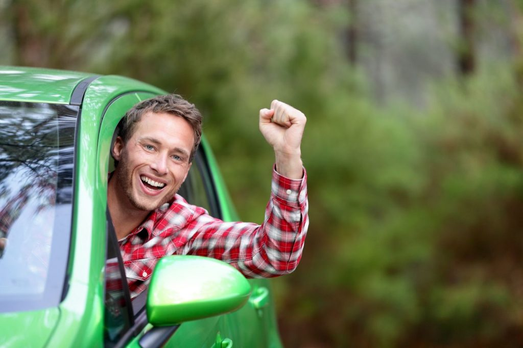 Green energy biofuel electric car driver happy and excited. Man